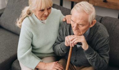 starsza kobieta pociesza starszego mężczyznę opierającego głowę na lasce