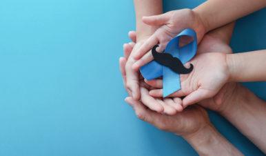 wiele splecionych dłoni trzymających niebieską kokardkę z czarnym wąsem