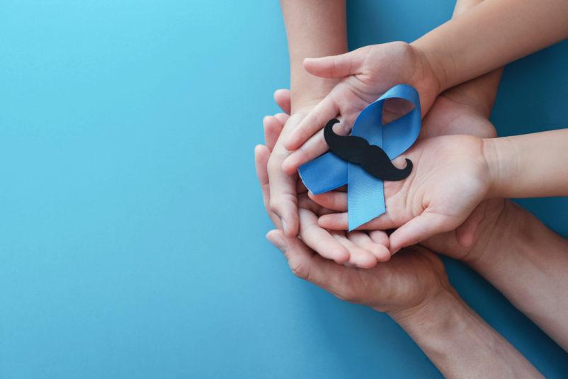 wiele splecionych dłoni trzymających niebieską kokardkę zczarnym wąsem