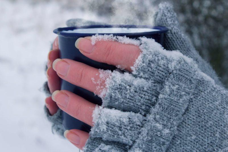 kobieta zimą trzyma gorący kubek