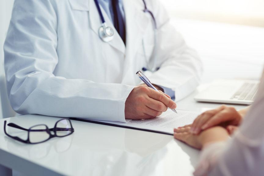 lekarz wypisujący kartę pacjenta wgabinecie