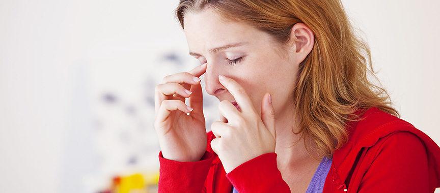 kobieta trzymająca się za nos zbliska